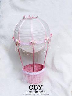 Este centro de mesa globo aerostático maravillosamente hecha a mano se hace usando una linterna de papel de Marfil que ha sido adornada con cinta de color rosa y encaje de color rosa adorno. Se ha decorado con perlas y color de rosa y marfil drapeado y adornado con lazos color rosa. La