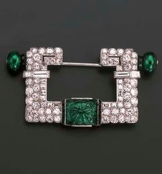 AN ART DECO EMERALD AND DIAMOND BROOCH, BY CARTIER  The central rectangular carved emerald within buff-topped onyx borders to the pavé-set and baguette-cut diamond U-shaped frame with emerald bead and onyx detail to each side, circa 1925