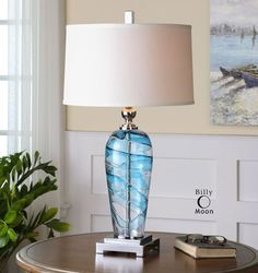 Seaworthy table lamp created of blown blue and clear glass accented with elegant polished nickel plated details.