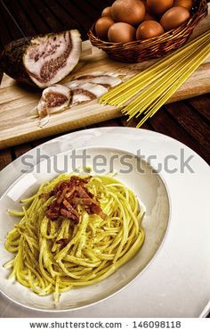 Italian traditional recipe, spaghetti alla carbonara with ingredients on background and a glass of red wine by MilaCroft, via ShutterStock