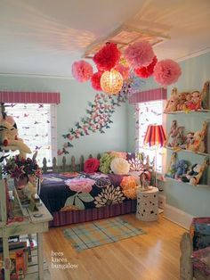 Decorating Ideas For Little Girl's Room: Colorful Little Girl's Bedroom Ideas In Fun Design — tissue paper pom pom lights, sheer butterfly curtains, pink valences, floral bedspread, blue and yellow rug, striped lamp, stuffed animals on shelves