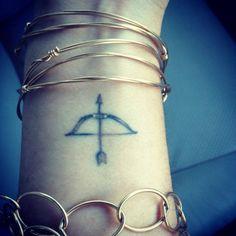 Wrist tattoo of a bow and arrow (Sagittarius) on Laura Wilson.