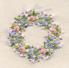 Close-up of embroidered wreath made with bullion knots, French knots & lazy daisies. Worked on a white cambric linen collar, these colors will coordinate with a variety of solids and prints for garment. Made by Trudy Horne.