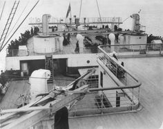 Historic photograph of Titanic from the after end of the superstructure looking aft towards the Poop Deck, taken by a local photographer during Titanic's arrival in Queenstown. Third class passengers can be seen at the rail.