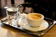 Viennese Coffee Melange A cup of coffee served the Viennese way, on a silvery tray and a glass of water with a downturned spoon