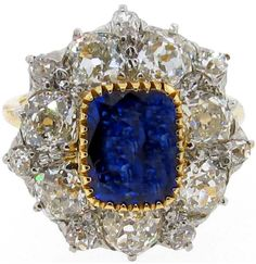 This sapphire and diamond ring was made in 1900. The center vivid blue cushion cut sapphire (approx. 2.25 cts) is surrounded by 14 old mine cut diamonds prong set in 14 kt. platinum (totaling approx. 3.2 cts). The shank is 14kt. yellow gold. This ring is for sale at Park Place Antique Jewelry, listing available via 1stdibs.