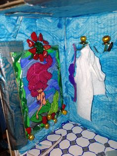 Stained glass of Ariel, and her bra and bathrobe hanging in the Little Mermaid themed bathroom. #Dollhouse #LittleMermaid