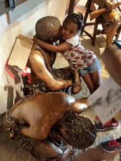 "When told of what happened to her ancestors this little girl hugged the statue and said, ""aww it will be alright."""