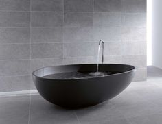 Modern Italian bathtub inspired by egg shape. Bathtub made from a single block of black K-plan: a compact, smooth, and resistant material that is pleasant to the touch and quick and easy to clean.