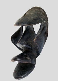 A Dan/Kran mask with a large, protruding snout, prominent hooknose, triangular eyes, pierced through, beneath an overhanging forehead, sacrification traces on top, an iron hook for fetish attachments, source: http://www.tribalartforum.com