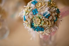 Gorgeous, glitzy teal & gold brooch bouquet with feather accents.