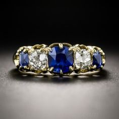 A classic late-Victorian (turn-of-the-century) five-stone ring, crafted in rich 18K yellow gold and featuring a trio of radiant royal blue cushion sapphires, totaling one-and-a-half-carats (one carat center stone), interspersed with a pair of bright sparkling antique cushion cut diamonds, together weighing .70 carat. Timeless, traditional elegance. Currently ring size 6.