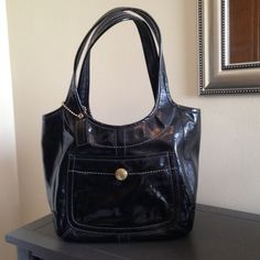 Coach Black Patent Leather Tote Coach Ergo Black Patent Leather Tote with Legacy Stripe lining. Outside snap pocket. Inside Zip Pocket. Perfect condition outside. Inside lining has a few ink marks. Beautiful bag! Coach Bags