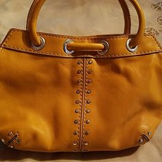 Authentic Micheal Kors small purse Mustard color bag with silver grammes. Perfect small date or club purse. Fits through wrist or in hand. Gently used Michael Kors Other
