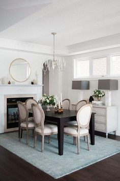 Blue and brown dining room features a whitewashed French candle chandelier illuminating a dark brown dining table lined with French round back dining chairs, Restoration Hardware Vintage French Round Fabric Side Chairs, atop a turquoise blue overdyed rug placed in front of a fireplace with round gold mirror.