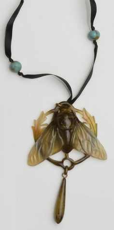 An Art Nouveau carved horn pendant. Modelled as a cicada with outstretched wings, heightened in graduating shades of green and brown, framed by foliage and suspending a tear-shaped drop below, to later ribbon suspension with turquoise-coloured paste bead spacers, unmarked, pendant length 12cm. #ArtNouveau #pendant