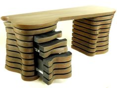 The Wave Desk is a really attractive office desk, created with the help of a new technique of slicing the wood. Two towers of sliced wood support the large surface. This office desk also features drawers and a pull-out work surface.