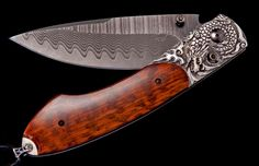 The Spearpoint 'Dwiirok' by William Henry  features a frame in hand carved Sterling Silver, inlaid with beautiful Snakewood.  The blade is black-coatedWave damascus with an extra strong core in ZDP-189; the one-hand button lock and the thumb stud are set with spinel.