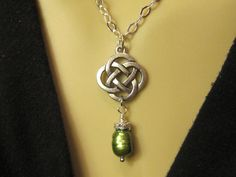 Eternal Knot Work Charm Necklace. Celtic Quarternary Knot Pendant and Green Freshwater Pearl. Celtic Jewelry.. $22.00, via Etsy.