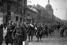 Victorious Soviet soldiers march through the Hungarian capital following the defeat of Axis Hungarian and German troops in the Siege of Budapest. The