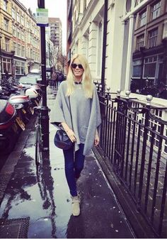 Claudia Schiffer does street style with a poncho, skinny jeans, ankle boots, and sunglasses from her very own line by Rodenstock.