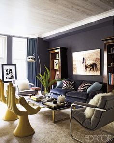 Rich gray walls and couch with zebra print pillows.