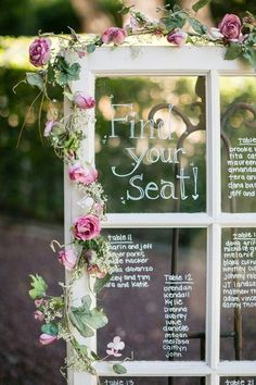 Trailing vines, greenery & white flowers {not pink!} on the window pane seating chart {Michael Anthony Photography}