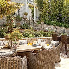 """This Laguna Beach garden features a terraced design that creates natural """"rooms"""" within the space. To the left is a relaxed dining area, and to the right a casual bar. If your space doesn't include terraced walls, consider delineating rooms with different flooring, plants, or styles of furniture. 20 Outstanding Outdoor Dining Rooms 