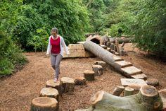 Woman walking along a log at the log trail