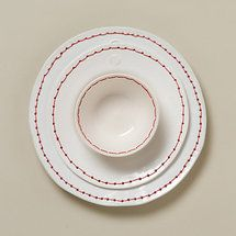 hand-thrown ceramic is stitched with a bright red rim of thread. absolutely gorgeous!