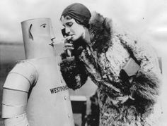 The mechanical man has been 'humanized' in some respects and taught some of the manners of polite society. The Westinghouse robot - Mr Willie Vocalite - shown in this photograph smokes cigarettes and obligingly 'gives a light' to his companion. Another robot in Pennsylvania State College with a glass throat and water lungs puffs cigars all day long and reports scientific facts about tobacco which the most expert human smokers could not find out.  photo taken on April 16th, 1931