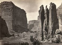 """Panoramic view of tents and a camp identified as """"Camp Beauty"""", rock towers and canyon walls in Canyon de Chelly National Monument, Arizona. Tents and possibly a lean-to shelter stand on the canyon floor, near trees and talus. Photographed in 1873. (Timothy O'Sullivan/Library of Congress)"""