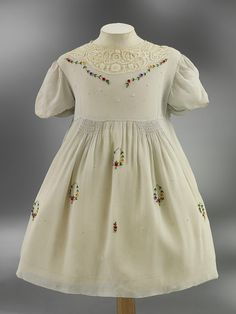 Circa 1938 rayon child's dress trimmed with lace, smocking, and embroidered flowers.