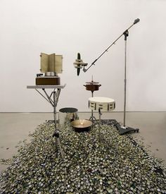 """""""Untitled (flat tambourine logarythm manual, snare drum, hi hat and bottle top, floor tom / bottle top, Mikrofonspinne)"""", 2012 by Michael Gumhold. Tripods, wood, canvas, springs, paint, parts of drum kit, cooking pot, lid, crown caps, mirror folie, wood, recordplayer, varnish, book, aluminium, recording studio tripod, screws, cucumber."""