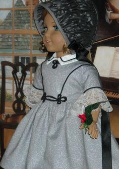 Period looking because: the arching bodice trim, frog at waist, small white collar, bonnet