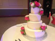 Fresh white and pink roses clustered on a beautiful tiered cake