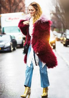 An oversized red fur coat is worn over a white blouse, with a black shoulder bag, blue jeans, and metallic heeled booties