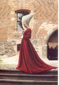 A Burgundian gown in red wool, lined with white linen, with white velvet cuffs and collar. a hennin headress with veils  Second half of the 15th century