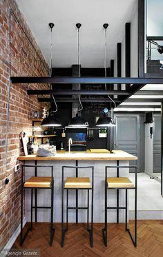Kuchnia przywodzi na myśl pofabryczne wnętrze - sprawiają to metalowe belki podtrzymujące antresolę, stare lampy przemysłowe (znalezione na Allegro) i instalacja biegnąca po ceglanej ścianie. Chłód tych industrialnych elementów ocieplają dębowe fronty szafek, blaty i półki. Część roboczą kuchni ze zlewozmywakiem zasłania podwyższony barek, który służy Dorocie również jako stół.