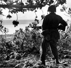Alone: A U.S. Marine, pictured in July 1944, looks at the bodies of dead Japanese soldiers killed during the battle for control of Saipan