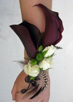 SO beautiful! Bridesmaids wore corsages instead of having a bouquet. mini calla lilies with accents of spray roses and button mums. Finished off with feathers.