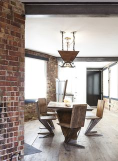 exposed brick wall in an open plan dining room with z-shaped wooden chairs by Nathalie Priem interiors photographer
