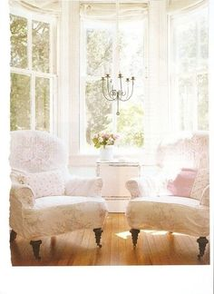 Gorgeous bay window with white chairs and wood floors.