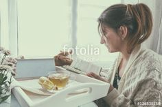 """Download the royalty-free photo """"Young woman in white sweater reading book near the window. Cup of tea, flowers and macaroons in tray on the table. Coloring and processing photo in vintage style."""" created by Victoria Kondysenko at the lowest price on Fotolia.com. Browse our cheap image bank online to find the perfect stock photo for your marketing projects!"""