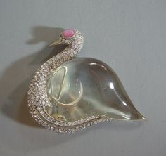 "TRIFARI jelly belly sterling swan brooch with Lucite belly, clear rhinestones and pink glass cabochon eyes all set in silver tone, 2-1/2"". Designed in 1944 by Norman Bel Geddes for Trifari."