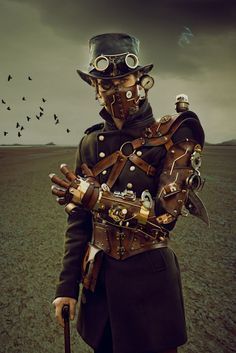 Steampunk man with leather mask and mechanical arm  - For costume tutorials, clothing guide, fashion inspiration photo gallery, calendar of Steampunk events, & more, visit SteampunkFashionGuide.com
