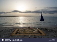 A scenic view of La Pelosa beach at sunrise in summer. A beach towel and umbrella in the sand with sea in background. - KDA85J from Alamy's library of millions of high resolution stock photos, illustrations and vectors.