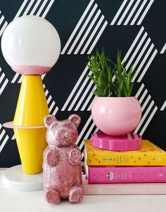 Pink and Yellow pop art inspired decor like a pink and yellow bauhaus or Memphis inspired table lamp, pink glitter bear, and a pink color blocked planter. Holographic Glitter, Pink Glitter, Pop Art Decor, Baby Girl Nursery Decor, Gummy Bears, Glass Globe, Pink Color, Yellow Table, Modern