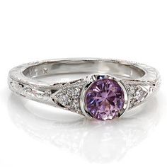 Sapphire Seville blends intricate details of handcrafted filigree and precise hand engraving. The 0.75 carat round cut natural purple sapphire is dressed with side stones in a triangular arrangement. Completing the antique style, milgrain edges frame the rings outline.  #engagement #wedding #ring www.knoxjewelers.biz