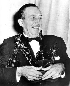 Hey, Walt, need a bag for those? Walt Disney cuddles with the four (count 'em) Oscars he won in a single night in 1954 (for short subject, two-reel; short subject, cartoon; documentary, short subject; and documentary, feature). Wow.